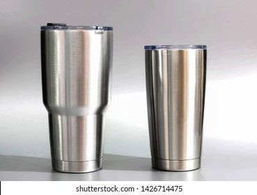 2 Cup cold storage. Tumbler glass cold store. Stainless steel thermos tumbler mug on gray background.