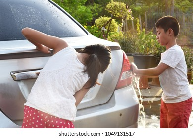 2 cute Southeast Asian Thai kid children sister and brother help each other cleaning washing car in orange morning light with copy space, household helping concept