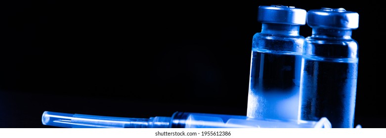2 doses of Sars-Kov-2 coronavirus vaccine in transparent glass ampoules, covered with frost and a disposable syringe, on a dark background, short focus, toning  - Shutterstock ID 1955612386