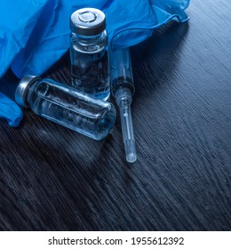 2 doses of Sars-Kov-2 coronavirus vaccine in transparent glass ampoules, covered with frost and a disposable syringe, on a dark background, short focus, toning  - Shutterstock ID 1955612392