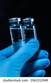 2 doses of Sars-Kov-2 coronavirus vaccine in transparent glass ampoules, covered with frost, on a dark background, short focus, toning  - Shutterstock ID 1961511949