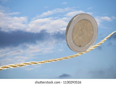 2 Euro coin balancing on golden rope in the sky.