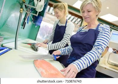 2 females preparing fish at fishmongers