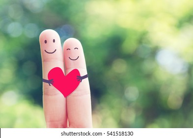 2 fingers holding red heart while smiling face with nature bokeh background. copy space. Happy couple in love.