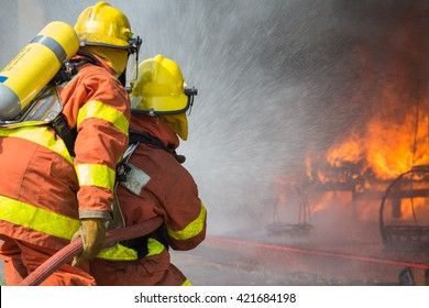 2 firefighters spraying water in fire fighting operation
