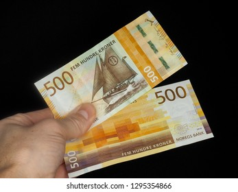 2 five hundred bill's of Norwegian kroner held by male hand at close-up isolated on black background with copy space