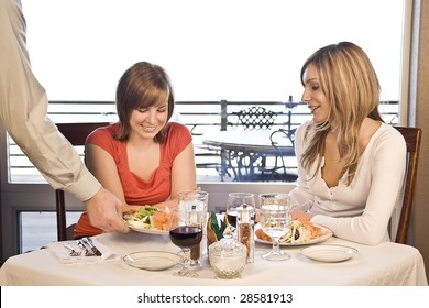 2 friends eating lunch at a cafe with a waiter brining food