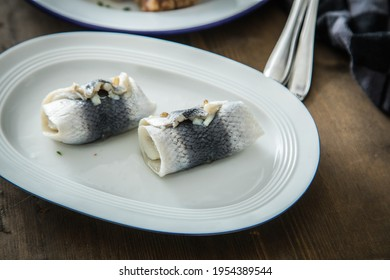 2 German Rollmops rolled pickled herring with gherkin onion filling on porcelain plate with cutlery, kitchen towel and dark wooden background