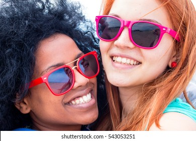 2 girls, best friends smiling together for a selfie photo. fashionable teenage afro hair girl with blond girlfriend holding to each other wearing colorful sun glasses friendship forever concept