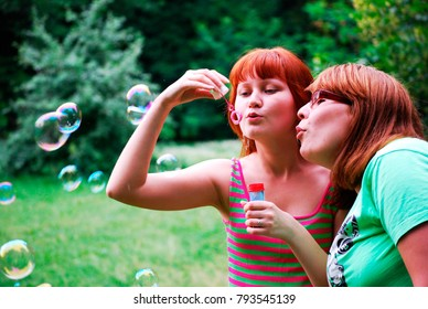 2 girls blow bubbles on the background of the forest