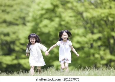 2 girls running hand in hand
