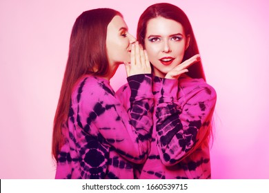 2 girls in the same things with bright makeup. Brunette girls, sisters, girlfriends, twins gossip, discuss, laugh. Women's power, March 8, Women's Day. copy space