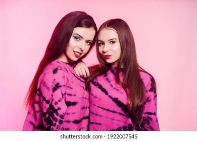 2 girls in the same things with bright makeup. Brunette girls, sisters, girlfriends, twins. Women's power, March 8, Women's Day. Clothing store for teens. Pink color in clothes, pink background.