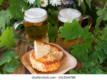 2 glasses of light beer with smoked cheese a bouquet of chamomiles and oak on a wooden table. Celebration of a traditional holiday in Latvia Ligo in June