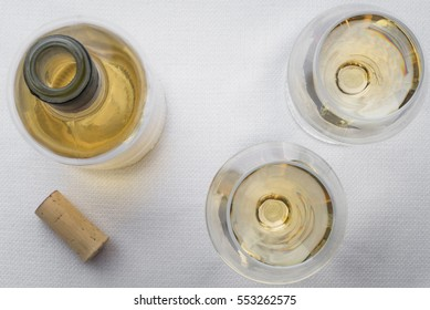 2 glasses of white wine with a bottle and cork on white linen table top