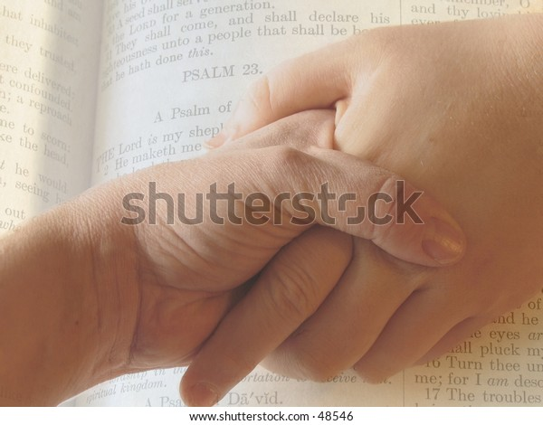 2 hands clasped together imposed on pages from Bible, 23 psalm.