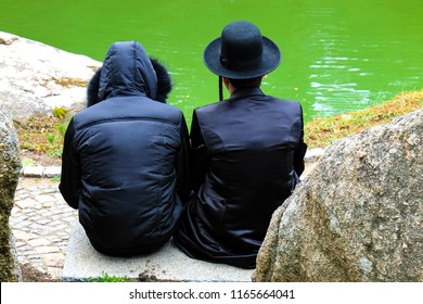 2 Hasidic  men, a family of Hasidic Jews, in traditional clothes read a prayer in the park in Uman, Ukraine, the time of the Jewish New Year, religious orthodox Jew