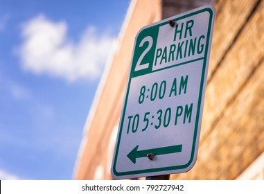 2 Hour Parking City Street Sign with building and blue sky in the background