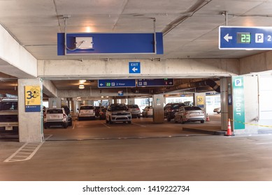 2 hour parking overhead neon sign at indoor airport parking lot displays number of available parking spaces. Available empty spots display counter information