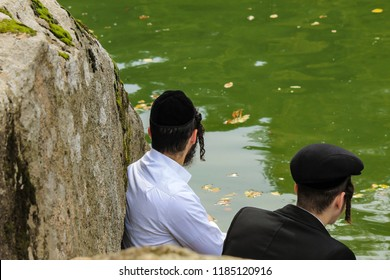 2 Jew boys, Hasidic Jews  family, in traditional black clothes  sitting  in the park, Uman,Ukraine, the time of the Jewish New Year, religious orthodox Jew