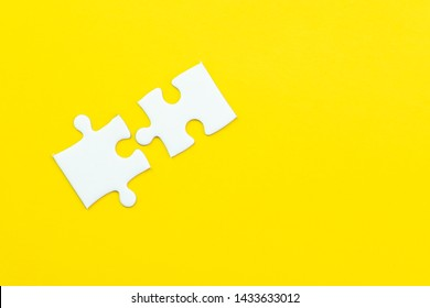 2 jigsaw puzzle on solid yellow background using as 2 important thing combine or working together to success or solve problem.