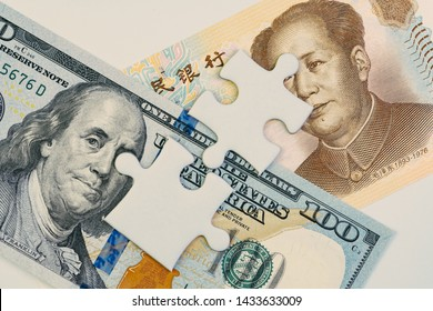 2 jigsaw puzzle on US America Dollar and Chinese Yuan banknotes using as tariff or trade war negotiation or future direction between the US and China concept.
