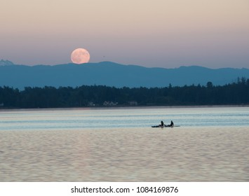 2 kayakers enjoy the moonrise over the mountains at sunset