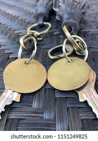 2 key rings with empty bronze plate on woven table