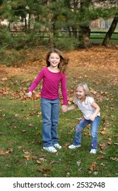 2 little girls playing outside in forest