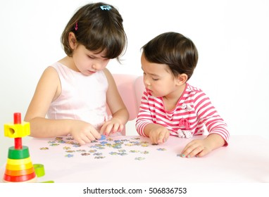 2 little girls playing together make a puzzle on pink table isolated on white