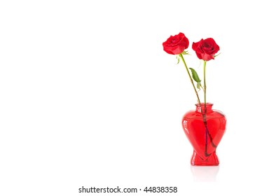 2 long stem red roses in a red glass heart shaped vase isolated on white with text/copy space