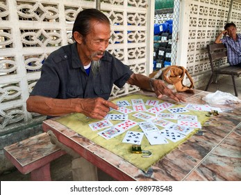 2 May 2016,Phrae,Thailand : A fortune-telling older man is predicting a fortune from cards to people passing through the city center near the hospital in exchange for a small amount of money.