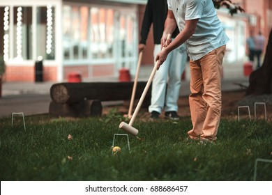 2 men playing croquet