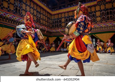 2 Monks dancing for colorful mask dance at yearly Paro Tsechu festival in Bhutan