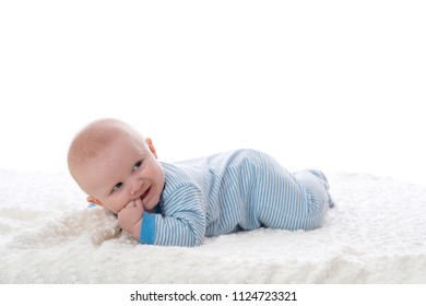 A 2 month old baby boy lying on his stomach on a white blanket. He is wearing pajamas, has his fingers in his mouth and has a mischievous grin. Shot in the studio on a white background.