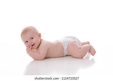A 2 month old baby boy lying on his stomach on a white, seamless background. He is wearing a plain, white diaper and has his fingers in his mouth. He is looking at the camera and grinning.