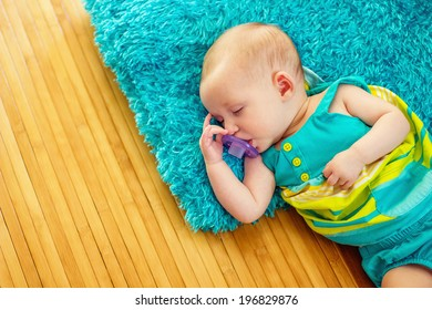 2 month old baby girl sleeping on a furry pillow and bamboo rug--image taken indoors using natural light (Reno, Nevada, USA)