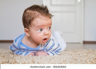 2 months old baby boy enjoying tummy time on the carpet at home.