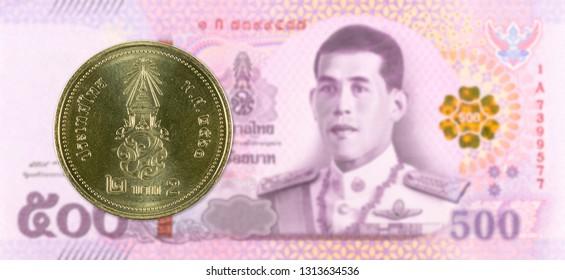 2 new thai baht coin against 500 new thai baht banknote