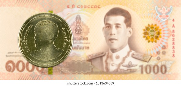 2 new thai baht coin against 1000 new thai baht banknote