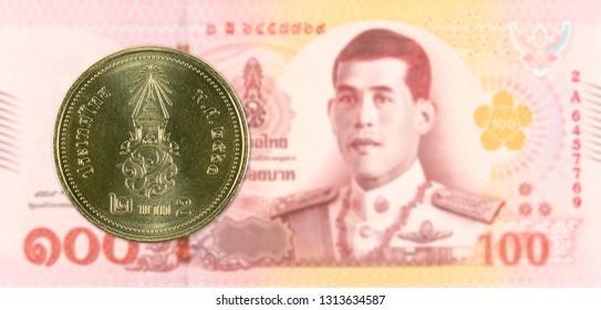2 new thai baht coin against 100 new thai baht banknote