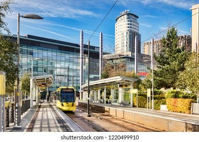 2 November 2018: Manchester, UK - Metrolink tram at Media City UK Station on a sunny autumn day with blue sky.