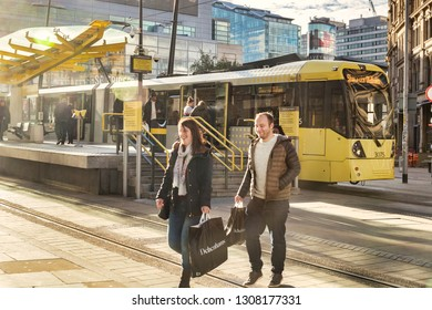 2 November 2018: Manchester, UK - Young couple smiling, with Debenhams shopping bags, in Exchange Square, with a Metrolink tram behind. Lots of flare.
