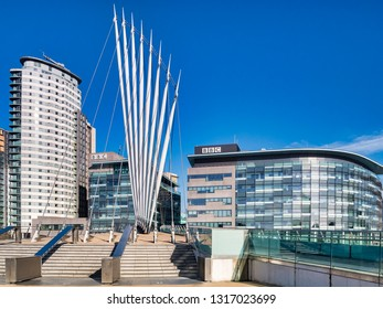 2 November 2018: Salford Quays, Manchester, UK -  BBC buildings, and the Media City Footbridge, which spans the Manchester Ship Canal, on a beautiful autumn day with clear blue sky.