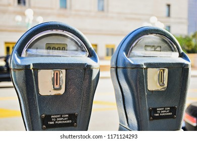 2 Parking Meters with a blurred street background, generic with no people