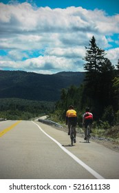 2 people cycling on a endless road in the mountains