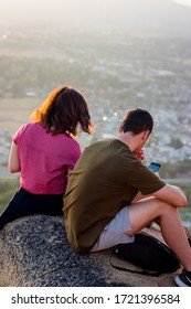 2 People hanging out on mount Rubidoux during Sunset in RIverside, California. USA