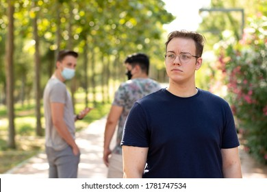 2 people with protective masks walking in the park are surprised and point to a person without a mask walking in the park and feel uncomfortable