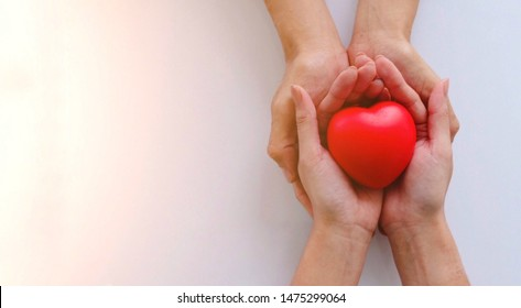 2 people stack their hands together with red rubber heart, with feeling of delivering or receiving of love, care, safe, thanks. Can be have as Valentine's Day, Birthdays or other day that is needed.