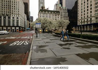 2 people walking through deserted 5th Avenue in NYC during Covid-19 pandemic